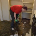 Vicki uses the power hammer to scrape 'peel and stick' off the kitchen floor.